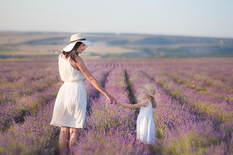 Young beautiful lady mother with lovely daughter walking on the lavender field on a weekend day in wonderful dresses and hats. Young beautiful lady mother with stock photos