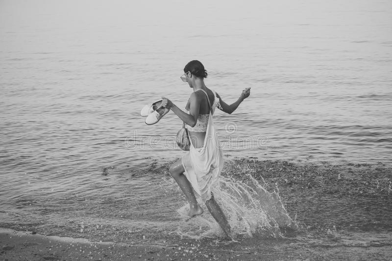 Young beautiful lady run on sea or ocean beach in water splash. Freedom concept. Woman carries shoes in hand and walks royalty free stock photography