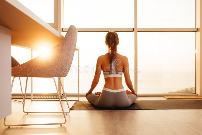 Young beautiful lady sitting in lotus pose on yoga mat and meditating near big windows at home. Portrait of young beautiful lady sitting in lotus pose on yoga stock photography