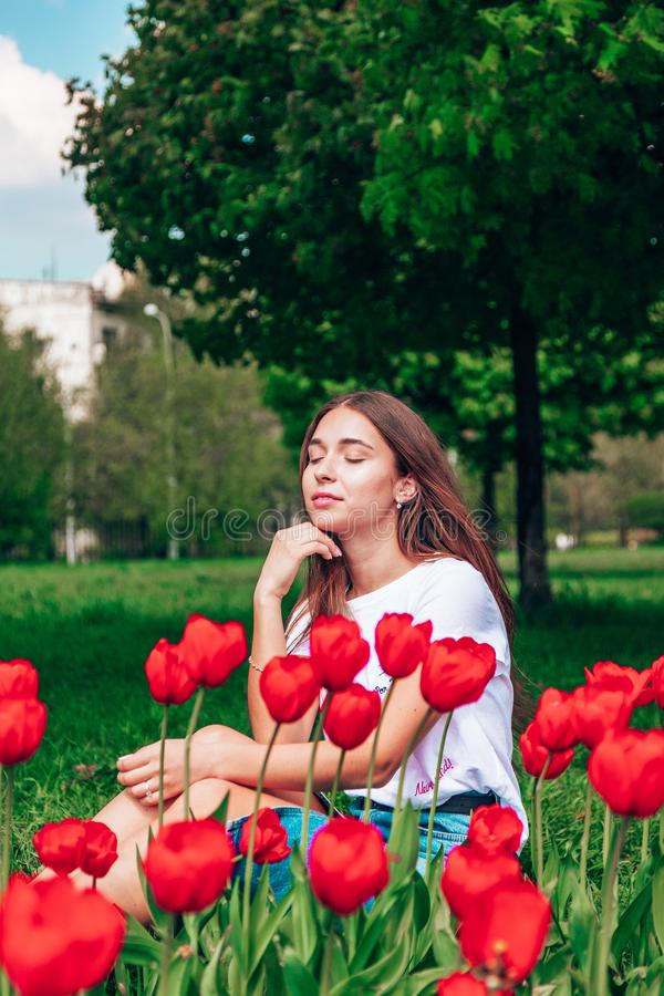 Young beautiful lady surrounded by tulips in spring royalty free stock photos