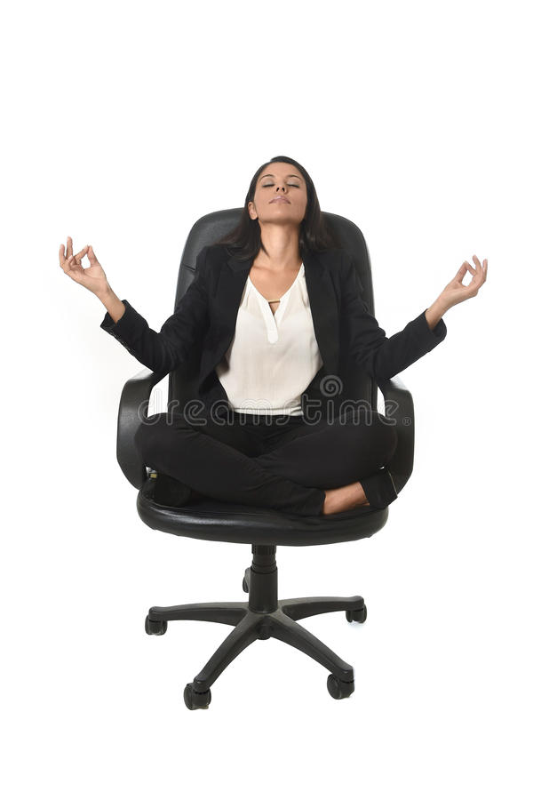 Young beautiful latin american business woman sitting at office chair in lotus posture practicing yoga royalty free stock images
