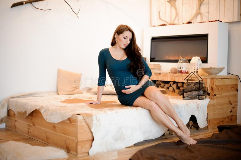 Young and beautiful long-haired pregnant woman sitting near the fireplace stock photo