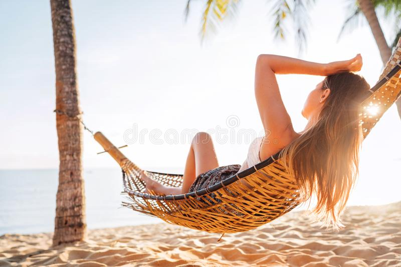 Young beautiful longhaired woman relax in hammok on the sand beach stock images