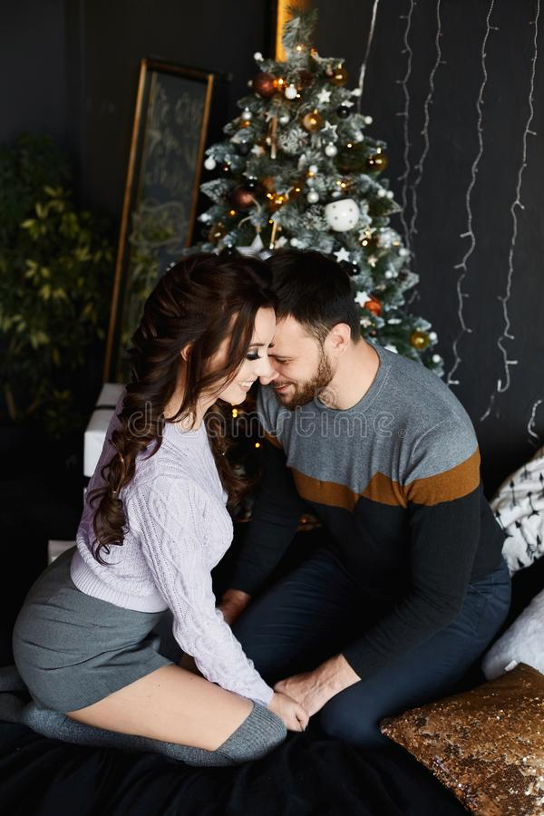 Young beautiful lovers in the Christmas interior. Handsome man and young beauty in stylish outfit spending Christmas stock photo