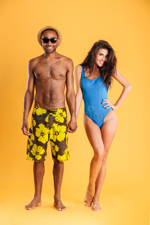 Young beautiful loving couple in beachwear holding hands. Isolated stock images