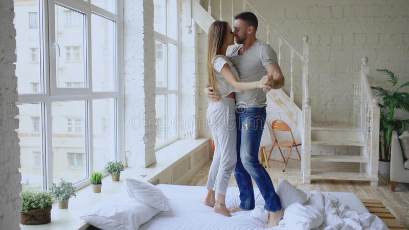 Young beautiful and loving couple dancing and kissing on bed in the morning at home stock images