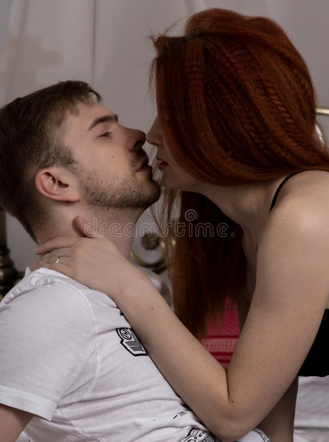 Young beautiful loving couple is embracing on a bed. ntimate image of sensual couple foreplay, kissing passionately stock photos