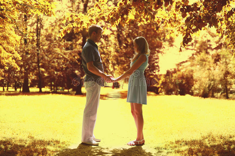 Young beautiful loving couple enjoys each other in autumn. Young beautiful loving couple enjoys each other in sunny warm autumn day royalty free stock photo