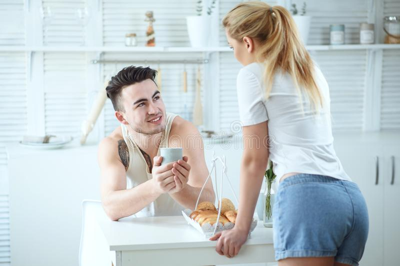 Young beautiful loving couple having breakfast and talking in the kitchen at home stock photo