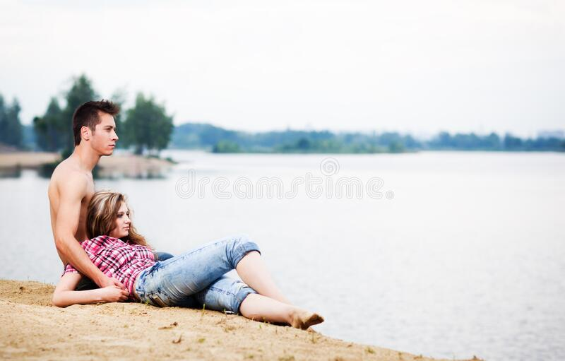 Young beautiful loving couple having rest on river shore on summer day with green nature at background stock photos