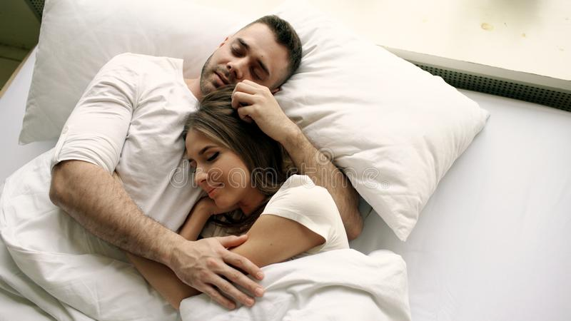 Young beautiful and loving couple kiss and hug into bed while waking up in the morning. Top view of attractive man royalty free stock image