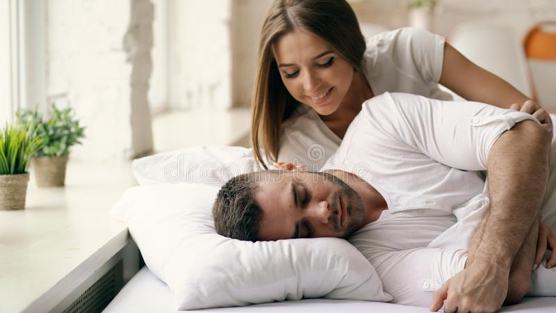 Young beautiful and loving couple wake up at the morning. Attractive woman kiss and hug his husband in bed. Young beautiful and loving couple wake up at morning stock photo