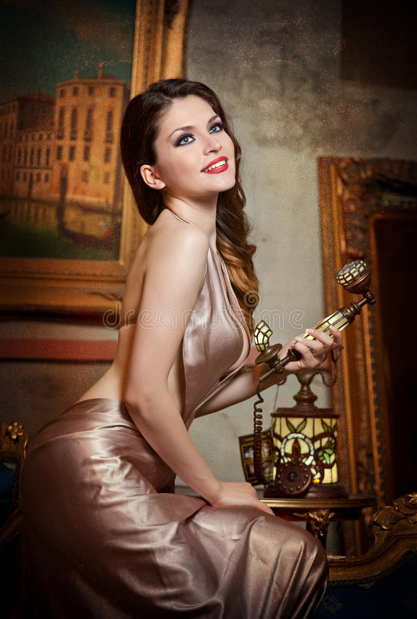 Young Beautiful Luxurious Woman In Elegant Dress Smiling Holding A Vintage Telephone. Beautiful Young Woman In Classic Scenery Stock Photo