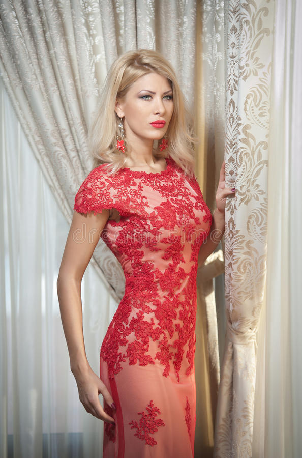 Young beautiful luxurious woman in long elegant dress. Beautiful young blonde woman in red dress with curtains in background royalty free stock image