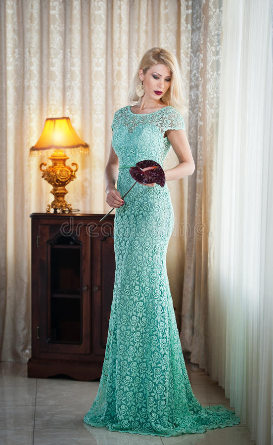 Young beautiful luxurious woman in long elegant dress. Beautiful young blonde woman in turquoise dress with curtains in background royalty free stock photo