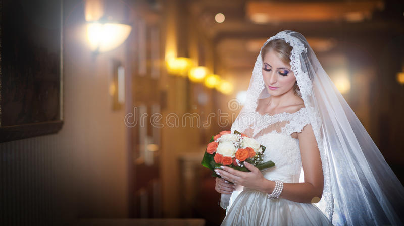 Young beautiful luxurious woman in wedding dress posing in luxurious interior. Bride with long veil holding her wedding bouquet stock image