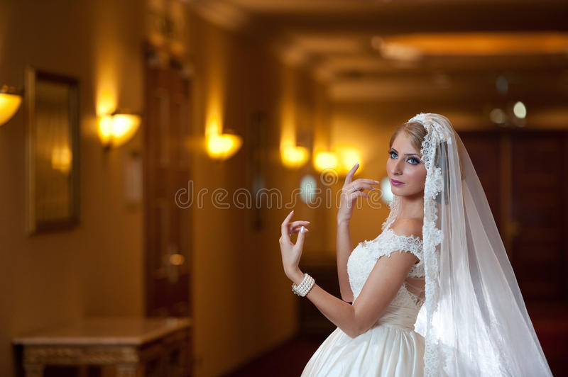 Young beautiful luxurious woman in wedding dress posing in luxurious interior. Gorgeous elegant bride with long veil. Seductive royalty free stock image