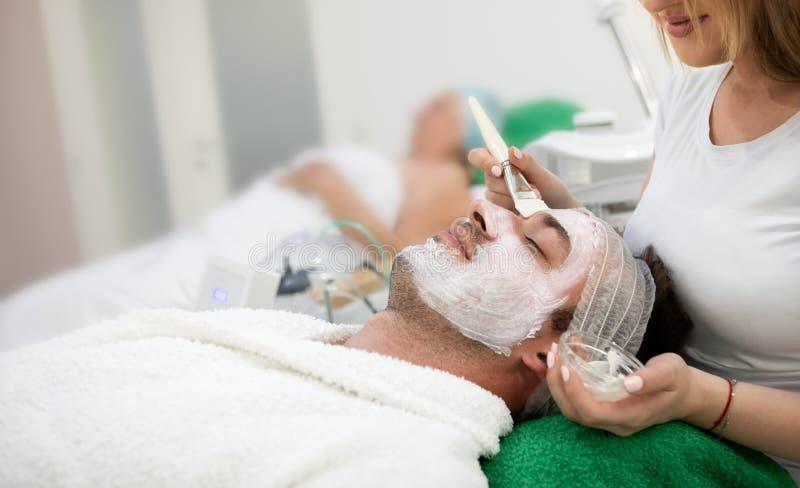 Man receiving hydration facial mask. Young beautiful men receiving hydration facial mask in spa beauty salon stock image