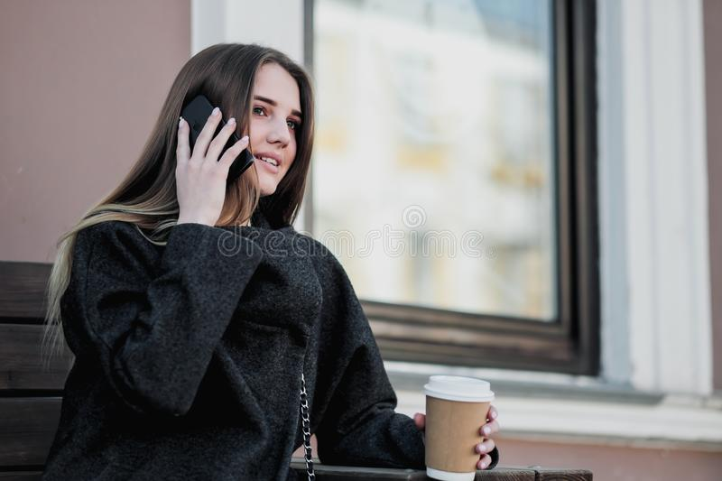 Young beautiful millenial girl in a coat is sitting on an outdor bench with a paper cup of coffee. Autumn or spring day royalty free stock image