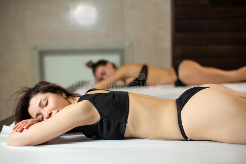 Young beautiful model girls on wooden loungers relaxing in a sauna. Beauty and wellness lifestyle royalty free stock photos