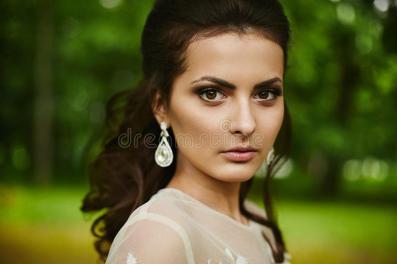 Young beautiful model woman with wedding hairstyle, with expensive earrings and with bright makeup royalty free stock photo