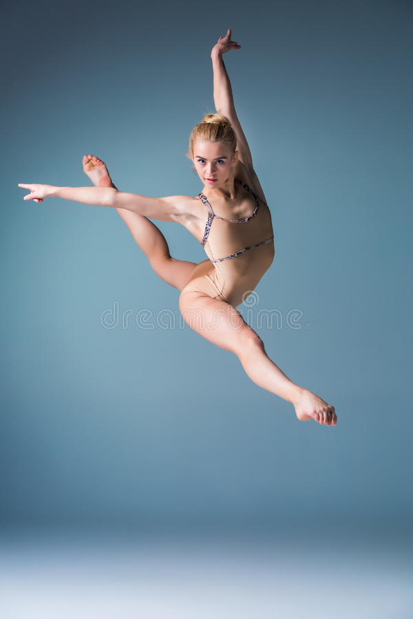 Young beautiful modern style dancer jumping on a studio background. Young beautiful modern style dancer jumping on a studio blue background royalty free stock photography