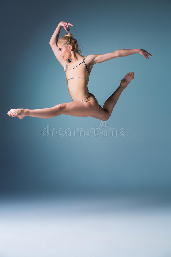 Young beautiful modern style dancer jumping on a studio background. Young beautiful modern style dancer jumping on a studio blue background royalty free stock photo