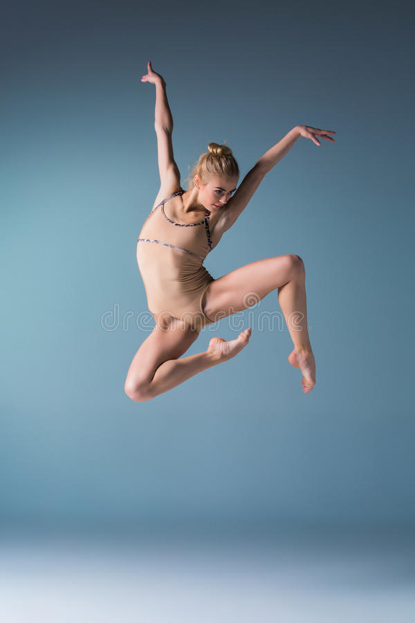 Young beautiful modern style dancer jumping on a studio background. Young beautiful modern style dancer jumping on a studio blue background stock images