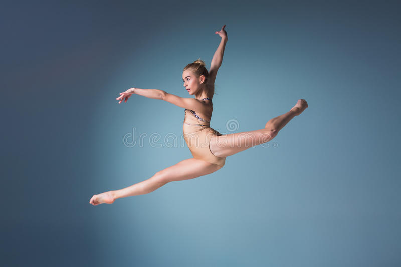Young beautiful modern style dancer jumping on a studio background. Young beautiful modern style dancer jumping on a studio blue background stock photography
