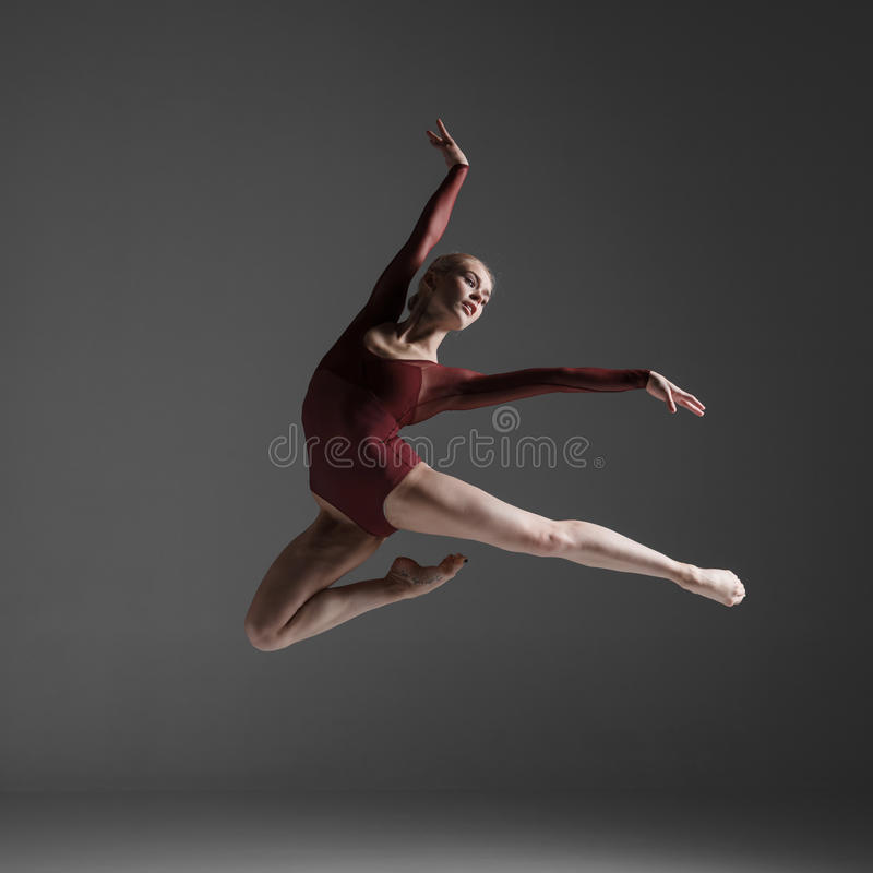 Young beautiful modern style dancer jumping on a. Studio gray background stock images