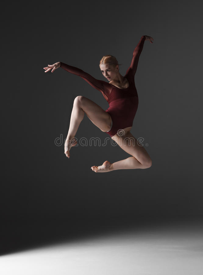 Young beautiful modern style dancer jumping on a. Studio gray background stock photography