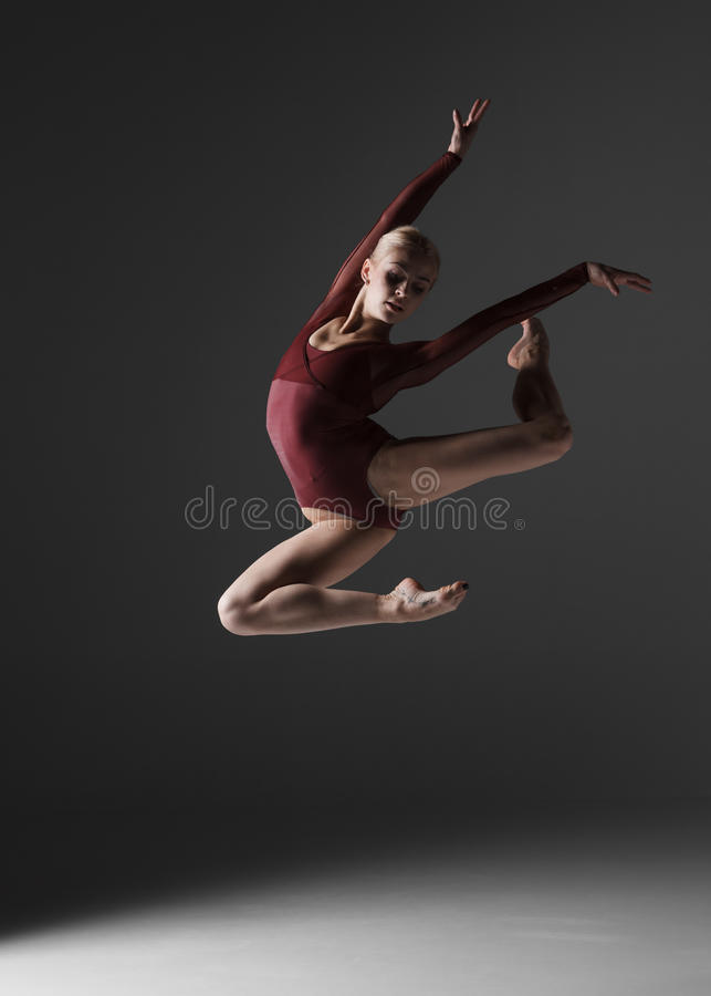 Young beautiful modern style dancer jumping on a. Studio gray background royalty free stock photo