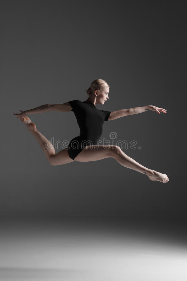 Young beautiful modern style dancer jumping on a. Studio gray background royalty free stock image