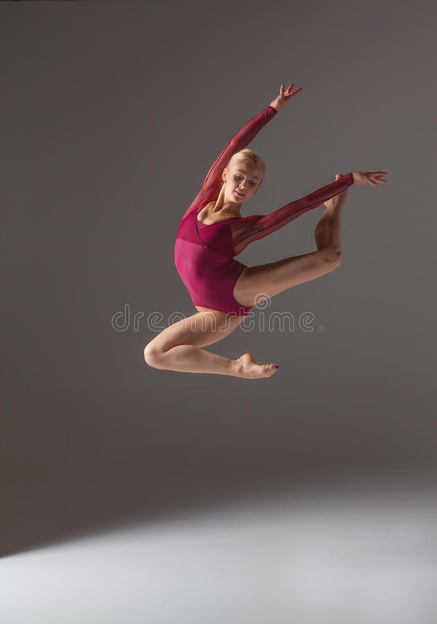 Young beautiful modern style dancer jumping on a. Studio gray background stock image
