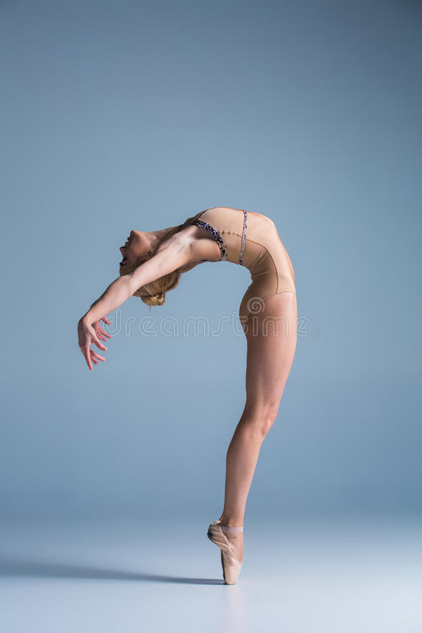 Young beautiful modern style dancer posing on a studio background stock photo