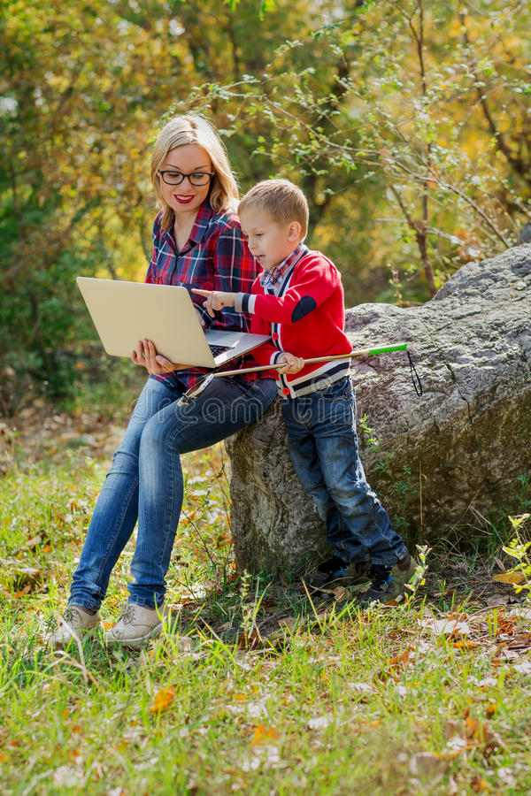 Young beautiful mom with glasses is holding a laptop on her hand. S and her son is showing something in the laptop, with a self-stick in his hands stock photography
