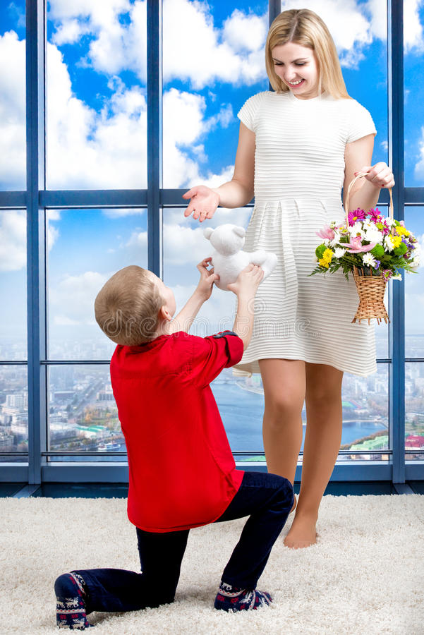 Young beautiful mother with her son and a bouquet of flowers. The child gives the mother a small Teddy bear, surprise.Spring conce. Son gives mom surprise.Little stock photo