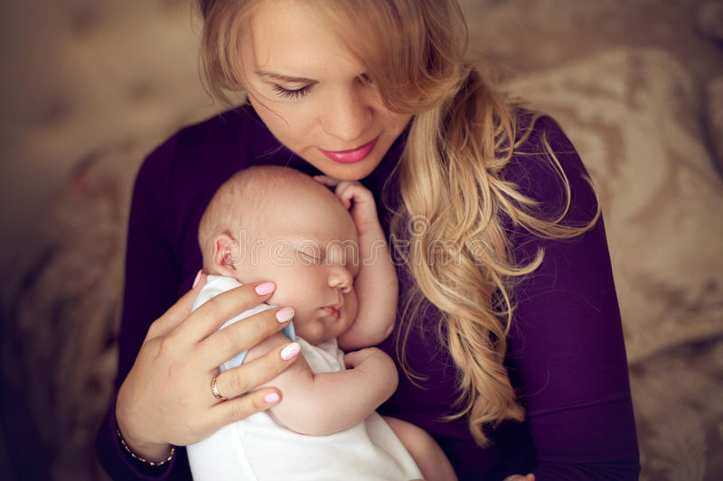Young beautiful mother holding sleeping newborn baby on hands in. The bedroom. The women lulls son pressed against his chest. Happy family at home royalty free stock image