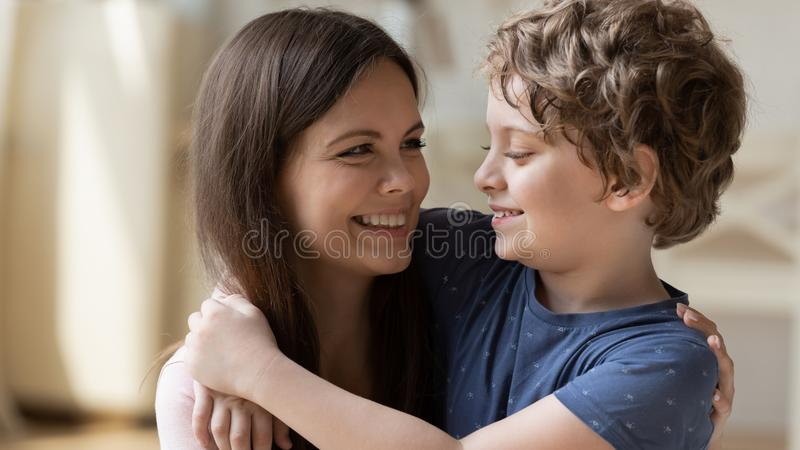 Young beautiful mother hugging little schoolboy son. stock photos