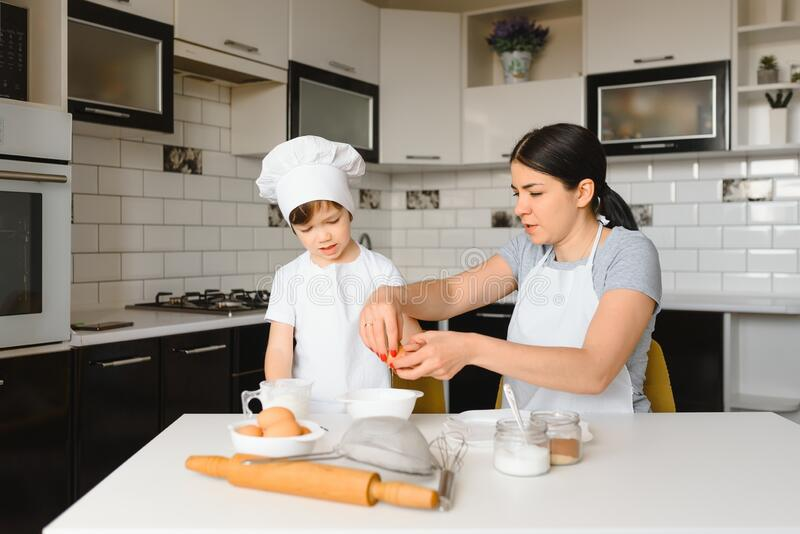 A young and beautiful mother is preparing food at home in the kitchen, along with her little son.  stock photos