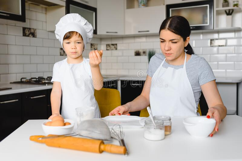 A young and beautiful mother is preparing food at home in the kitchen, along with her little son.  stock images