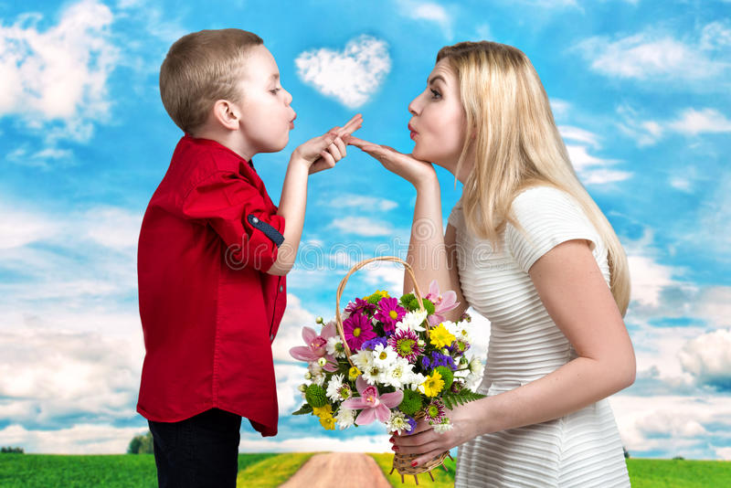 Young beautiful mother and son blow kisses .A woman and a boy with a bouquet,a basket of flowers. Spring concept of family vacati royalty free stock photo