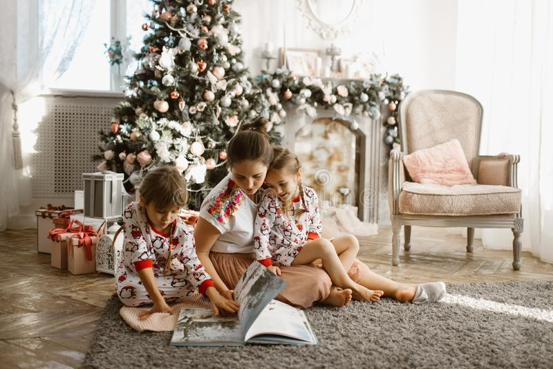 Young beautiful mother with two little daughters sit on the carpet and read book near the New Year`s tree with gifts in stock images