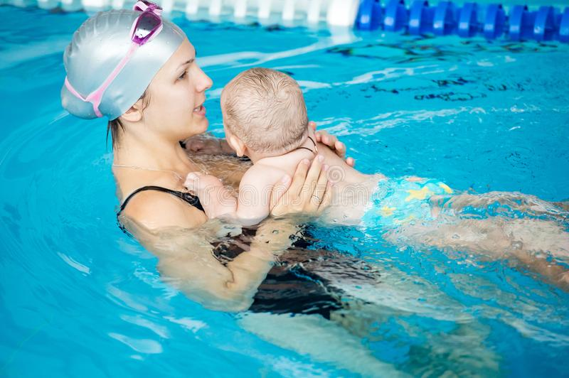 Young beautiful mother visit a swimming pool with her little son royalty free stock images