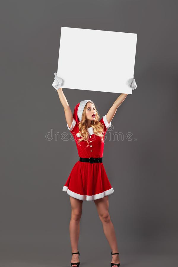 Young and beautiful mrs.Santa Claus dressed in the red robe, Santa`s hat, gloves and high heels holds the white canvas stock photos
