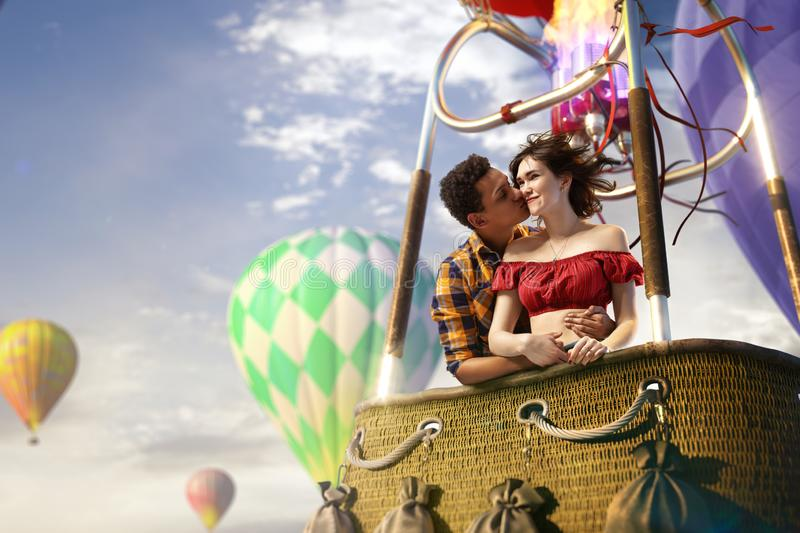 Young beautiful multiethnic couple kissing in the hot air balloon. stock photography