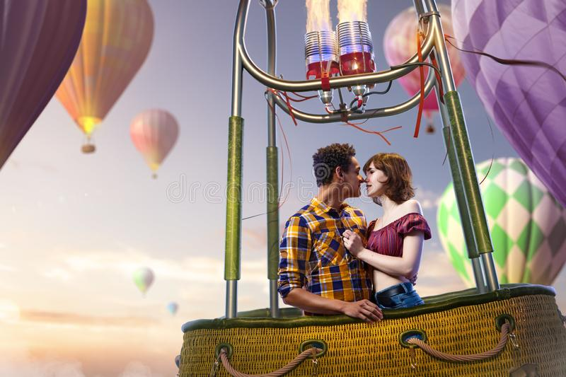 Young beautiful multiethnic couple kissing in the hot air balloon. Very romantic picrure royalty free stock image