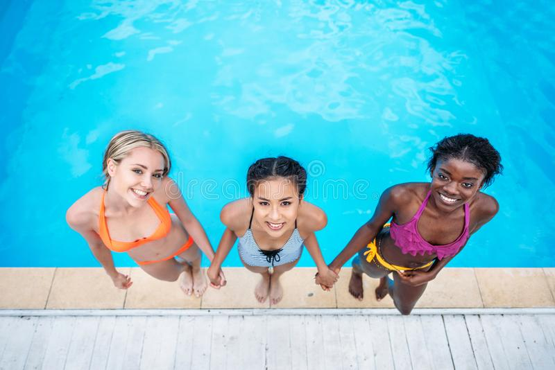 Young beautiful multiethnic women standing near swimming pool. At resort stock image