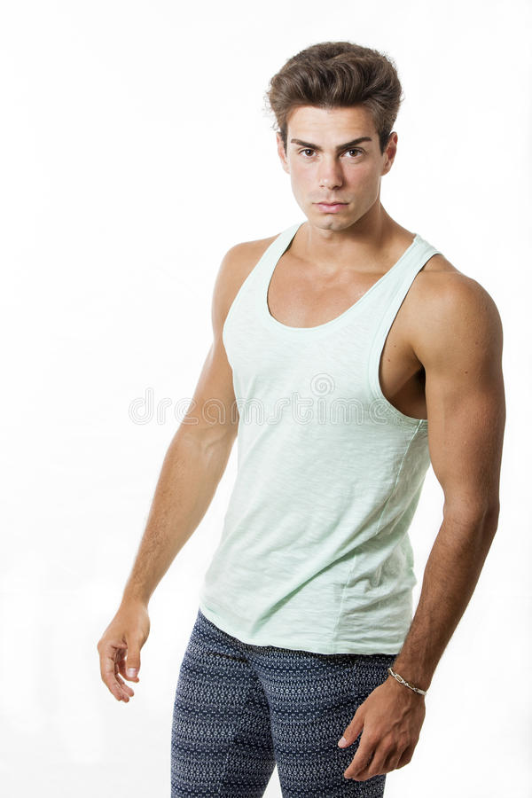 Young beautiful and muscular man model outfit. A beautiful young model man poses in studio with white background. He has a very toned and muscular physique and stock image