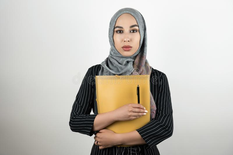 Young beautiful Muslim business woman wearing turban hijab headscarf holding folder with documents and pen isolated royalty free stock images